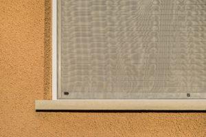 Closeup  Fliegengitter vor einem Fenster mit geschlossenem Rolll